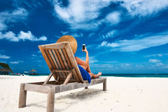 Young woman with mobile phone at the beach. Young woman in hat with mobile phone at the beach royalty free stock photography