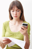 Young Woman With Mobile Phone And Bill Looking Worried Stock Photography