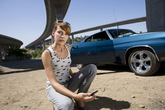 Young woman with mobile phone crouching by car, portrait Stock Image