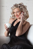 Young woman  with mobile phone and cup of coffee. Royalty Free Stock Image