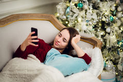 Young woman with mobile phone home lying on a sofa in front of fir tree Royalty Free Stock Image