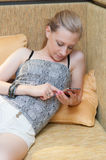 Young Woman with Mobile Phone in Livingroom Stock Photos
