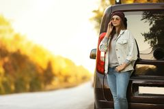 Young woman with mobile phone near car royalty free stock photography