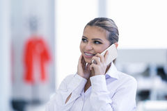 Young woman with mobile phone in the office Royalty Free Stock Photo