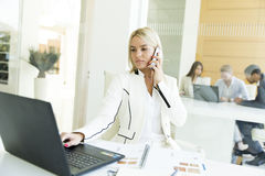 Young woman with mobile phone in the office. Young women with a mobile phone in the office Royalty Free Stock Photo