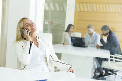 Young woman with mobile phone in the office Royalty Free Stock Photography