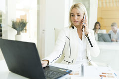 Young woman with mobile phone in the office. Young women with mobile phone at the desk in the office Royalty Free Stock Image