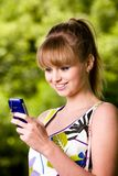 Young woman with mobile phone outdoors. Smiling blond young woman with mobile phone outdoors Royalty Free Stock Images