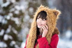 Young woman on mobile phone outdoors in wintertime. Portrait of smiling beautiful young woman in red winter coat and funny hat with ears holding cellphone in Stock Images