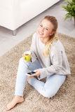 Young woman with mobile phone. Portrait of young happy blond woman sitting at home while drinking tea and checking e-mails on her mobile phone Royalty Free Stock Photography
