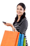Young woman with mobile phone and shopping bags Stock Images