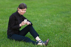 Young woman with mobile phone sitting on grass. Young happy smiling business woman resting on break, sitting on grass on lawn, holding cellphone, looking at Royalty Free Stock Photography