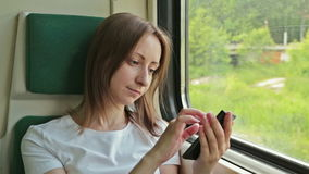 Young woman with mobile sitting on the train stock video