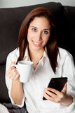 Young woman with the mobile on the sofa at home Stock Photo