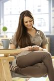 Young woman with mobilephone. Young woman using mobilephone at home, sitting on chair, writing text message, smiling happy Royalty Free Stock Photo