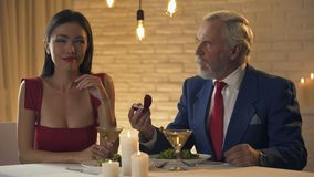 Young woman mocking at old oligarch proposing marriage, relationship for money. Stock footage stock footage
