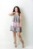 Young woman model wearing dress. Beautiful young woman model wearing dress standing over white wall Stock Photo