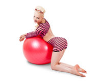 Young woman in modern attire posing with exercise ball Stock Image