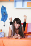Young woman in modern bedroom. Young woman lying on bed with knees bent and feet up, using cellphone, smiling, dimples Stock Photo