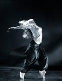 Young woman modern dance. Dark blue tint stock photography