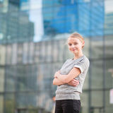 Young woman in modern glass office interior Stock Image