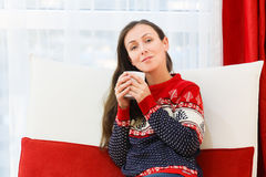 Young woman in modern interior living room drinks coffee at red Royalty Free Stock Photo