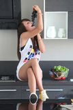 Young woman in modern kitchen, eating bunch of grapes. Young woman in modern kitchen, sitting on counter, eating bunch of grapes, playful, yellow sneaker Stock Photo