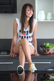Young woman in modern kitchen. Pretty young woman in modern kitchen, sitting on counter next to bowl of vegetables, legs crossed Stock Image