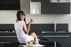 Young woman in modern kitchen. Sitting on table, holding apple, with fruit, smiling, dimple, looking over shoulder Royalty Free Stock Images