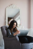 Young woman in modern luxury apartment, sitting comfortable in armchair holding computer on her laps, relaxing, working Royalty Free Stock Photo