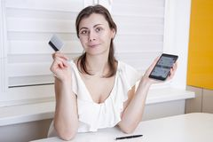 Young woman with modern smartphone and plastic credit card in hands. Online shop application on mobile phone and card for shopping Stock Image