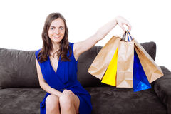 Young woman on modern sofa with a bunch of shopping bags Stock Photo
