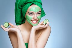 Young woman with moisturizing cream on her face and slices of cucumber. Royalty Free Stock Photo