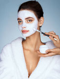 Young woman with moisturizing facial mask and hands of the beautician. Stock Photos