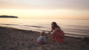Young woman mom in dress walks along the seashore at sunset with a small daughter stock video footage