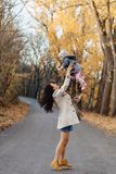 Young woman mom play with little daughter at autumn park road stock photo