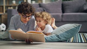 Young woman mommy reading book to curious boy discussing story on floor at home. Young woman mommy is reading book to curious boy discussing story lying on floor stock video