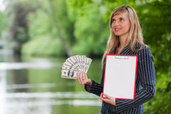 Young woman with money and clipboard. Royalty Free Stock Photos