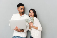 Young woman with money dreaming. Young women with money dreaming while her men using laptop isolated Stock Photography
