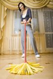 Young woman with mop. Woman standing in room with mop. Focused on mop. Looking at camera.Whole body. Low angle view royalty free stock images
