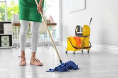 Young woman with mop cleaning floor. In office stock photo