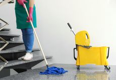 Young woman with mop cleaning. Stairs royalty free stock image