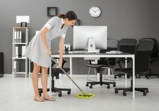 Young woman mopping floor. In office Royalty Free Stock Photos