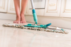 Young Woman Mopping Kitchen Floor. Low Angle View of Young Woman Mopping Kitchen Floor with Focus on Shiny Clean Floor and Mop Royalty Free Stock Photo