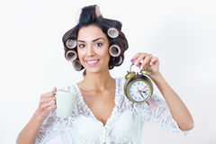 Young woman morning rush with coffee, clock and hair curlers. Morning rush. Beautiful woman in hair curlers holding cup of coffee in one hand and a clock in the Stock Photo