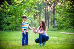 Young woman mother applying insect repellent to her son before forest hike beautiful summer day or evening. Protecting children. Young women mother applying royalty free stock photo