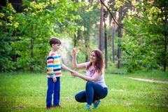 Young woman mother applying insect repellent to her son before forest hike beautiful summer day or evening. Protecting children. Young women mother applying royalty free stock photography