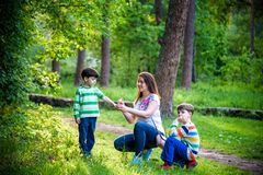 Young woman mother applying insect repellent to her two son before forest hike beautiful summer day or evening. Protecting. Young women mother applying insect royalty free stock photography