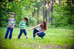 Young woman mother applying insect repellent to her two son before forest hike beautiful summer day or evening. Protecting. Young women mother applying insect stock photos