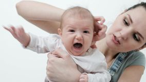 Young woman mother in denim overalls holds a baby child in her arms. White background in the studio. Happy family, baby crying stock video footage